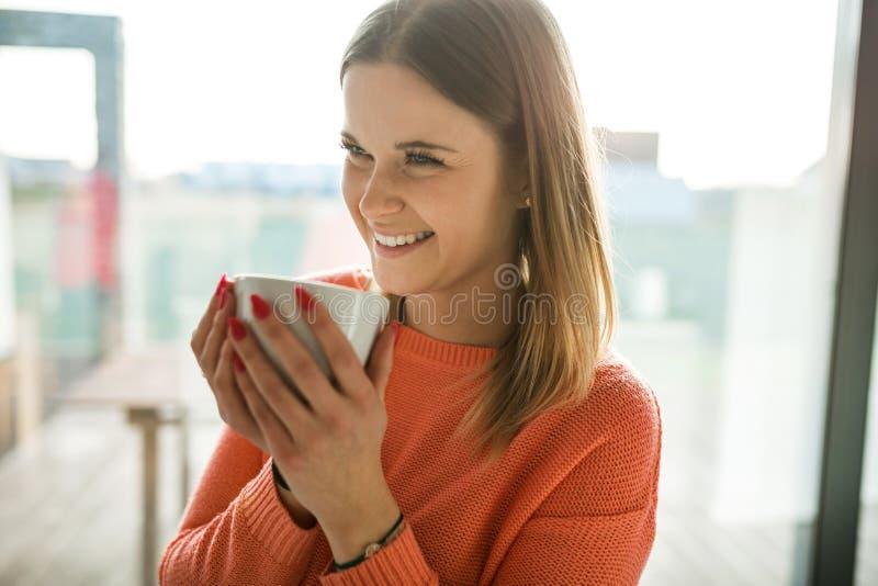 Ładna młoda kobieta trzyma filiżankę herbaciany śmiać się obraz stock