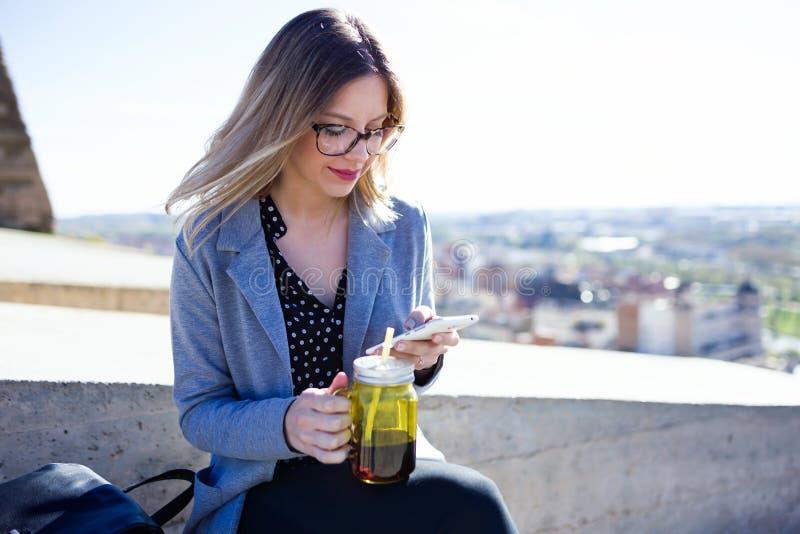 Ładna młoda kobieta używa jej telefon komórkowego w ulicie podczas gdy pijący sok fotografia royalty free