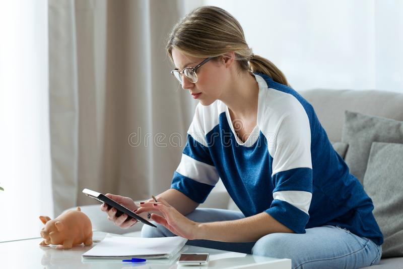 Ładna młoda kobieta używa kalkulatora i liczenia jej oszczędzania podczas gdy siedzący na kanapie w domu zdjęcie royalty free