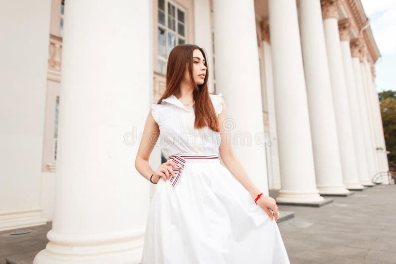 Ładna młoda kobieta w białej modnej sukni pozuje blisko kolumny fotografia royalty free