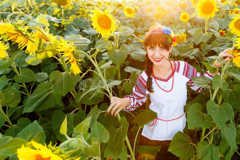 Ładna młoda kobieta w broderii na słonecznikowym polu zdjęcie stock
