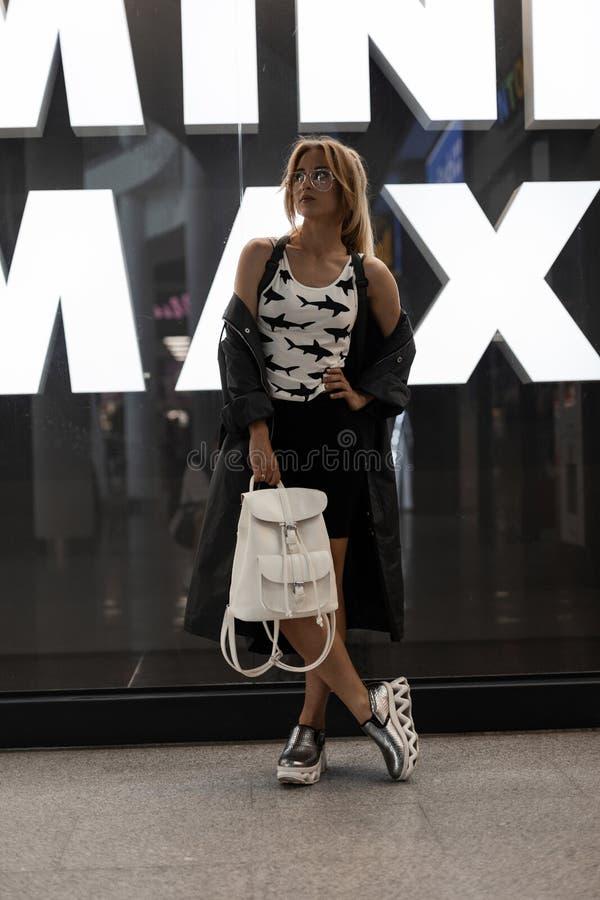 Ładna młoda kobieta w eleganckich szkłach w koszulce z wzorem w długiej lato kurtce w srebra modnych butach w spódnicie zdjęcia royalty free