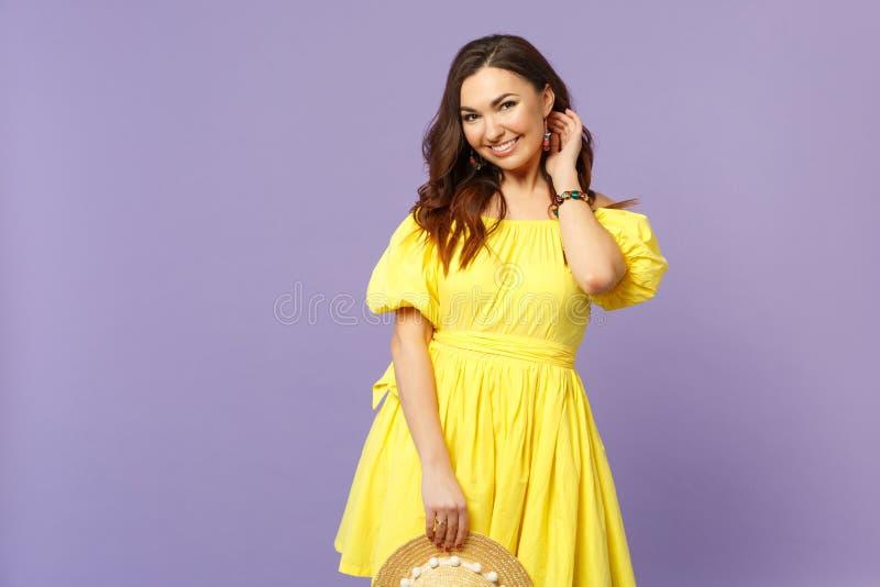 Ładna młoda kobieta w kolor żółty sukni chwyta lata kapeluszu, przyglądająca kamera, utrzymuje rękę na włosy na pastelowym fiołku obraz royalty free