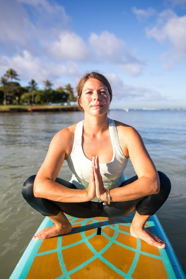 Ładna młoda kobieta w medytaci na wodzie przy ałunu Moana stanem zdjęcie royalty free