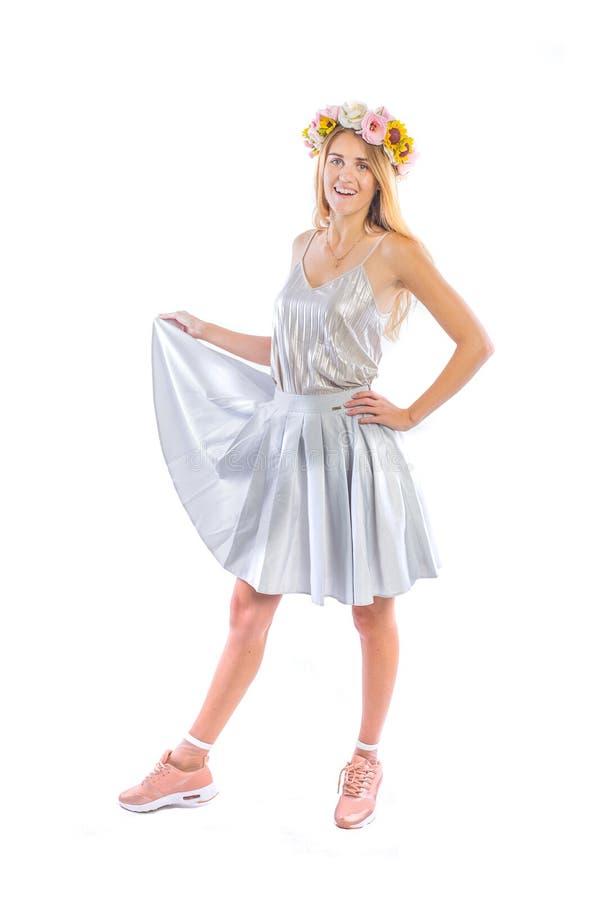 Ładna młoda kobieta w srebro plisującej spódnicie trzyma krawędź spódnica z jeden ręką w różowych sneakers i a, obrazy royalty free