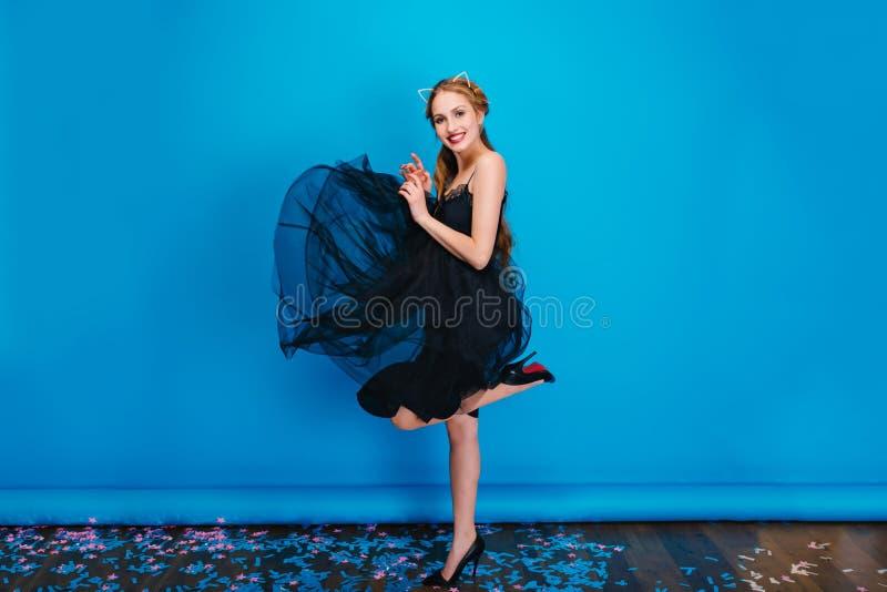 Ładna młoda kobieta w trzepotliwej czerni sukni, pozujący na błękitnym tle, tanczy przy przyjęciem Blondynka włosy, jest ubranym zdjęcia royalty free