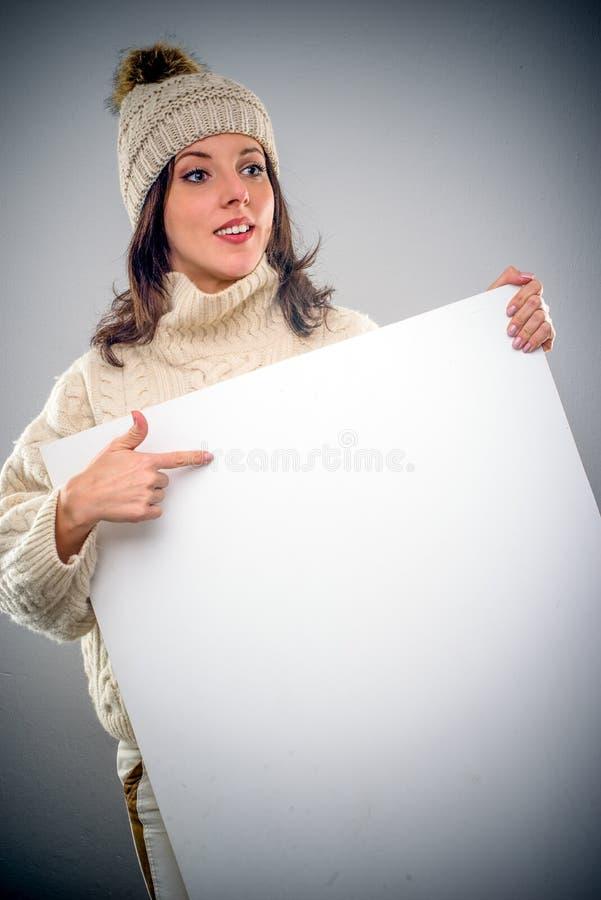 Ładna młoda kobieta wskazuje pusty znak obraz stock