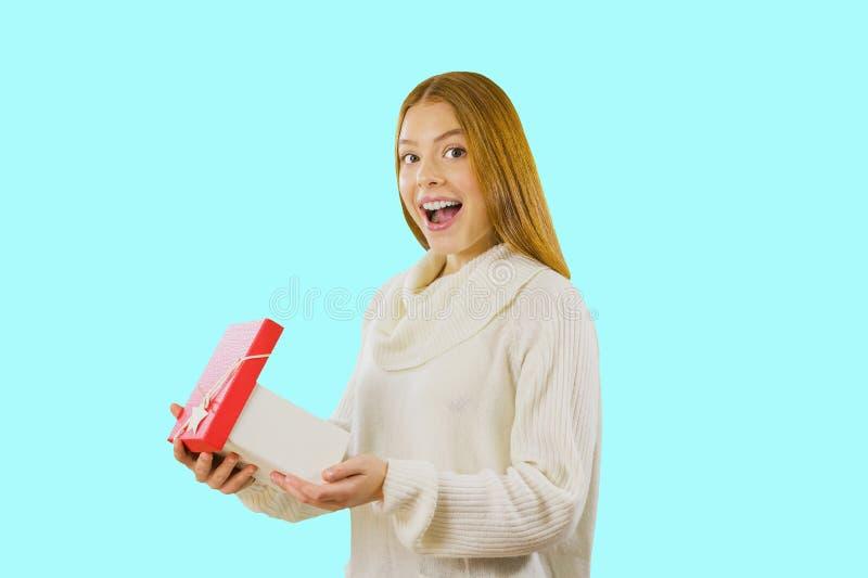 Ładna młoda kobieta z czerwonym włosy w białym pulowerze pozuje z prezenta pudełkiem Portret młoda dziewczyna która trzyma otwart zdjęcia stock