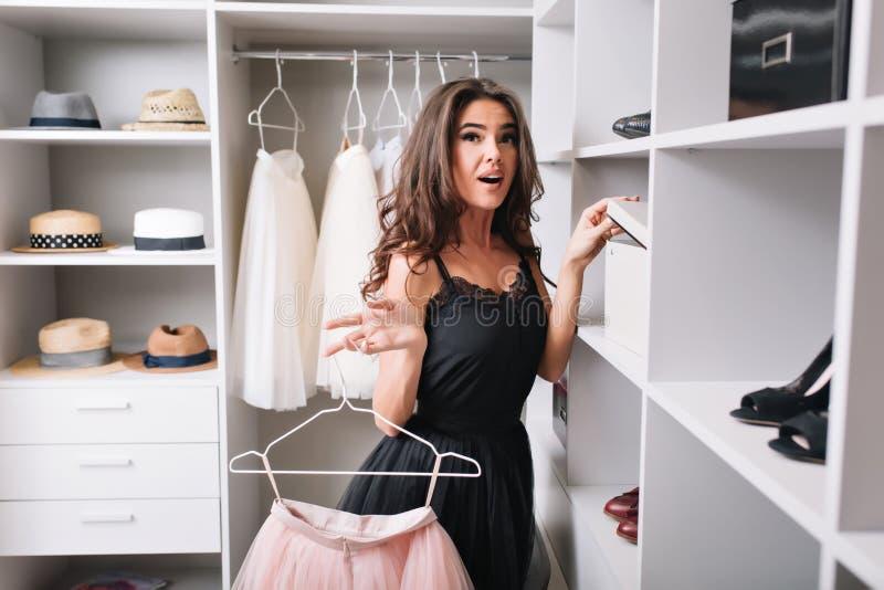 Ładna młoda kobieta z zdziwioną spojrzenie pozycją w ładnej garderobie, ciekawiącej, trzymający różowy puszystego co jest wśrodku obraz stock