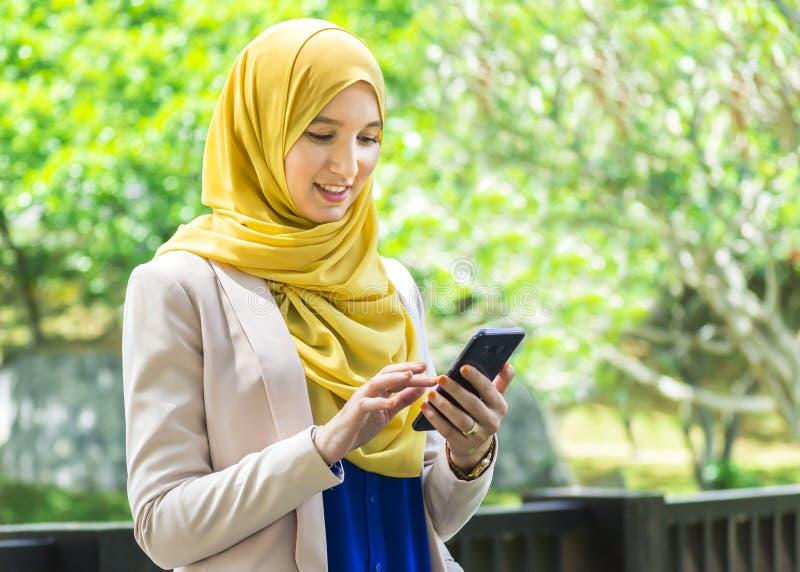 Ładna młoda muzułmańska kobiety przesyłanie wiadomości używać smartphone zdjęcie stock