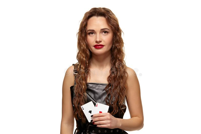 Ładna młoda rudzielec lub brązowowłosa kobiety mienia para as w czarnej skóry sukni odizolowywającej na bielu obraz stock
