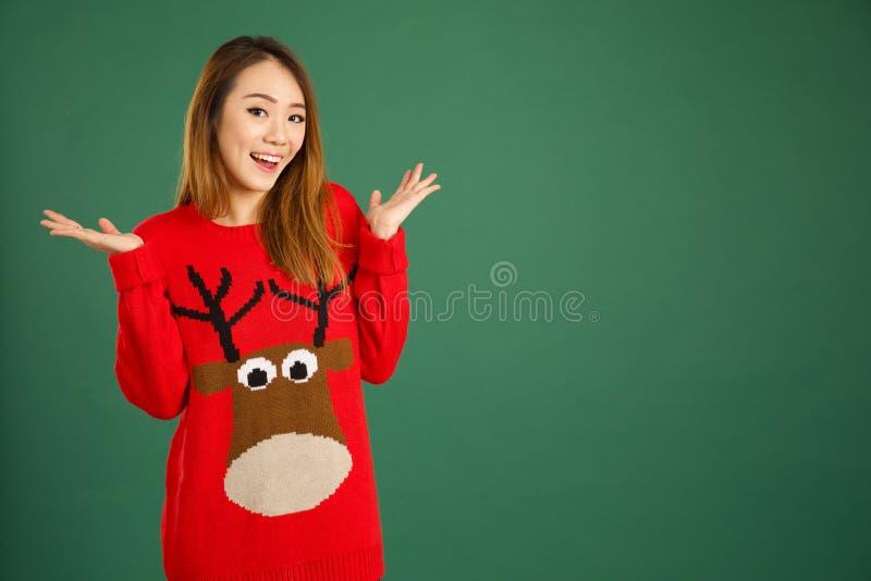 Ładna młoda singapurska dziewczyna jest ubranym Bożenarodzeniową bluzę i smili fotografia royalty free