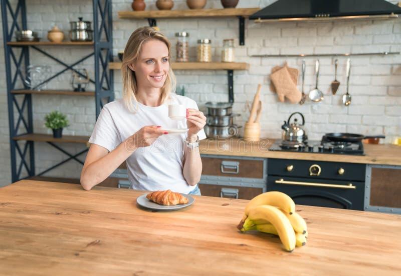 Ładna młoda uśmiechnięta kobieta jest siedząca w kuchni w domu, mieć śniadanie, pijący kawę z croissants i patrzeć zdjęcia royalty free