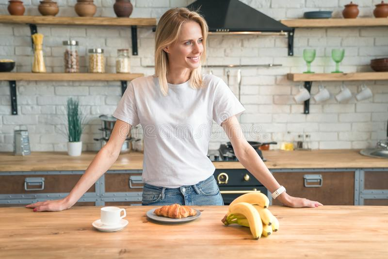 Ładna młoda uśmiechnięta kobieta przygotowywa śniadanie w kuchni w domu, patrzejący daleko od ranek kawa, croissants, banany zdjęcie stock