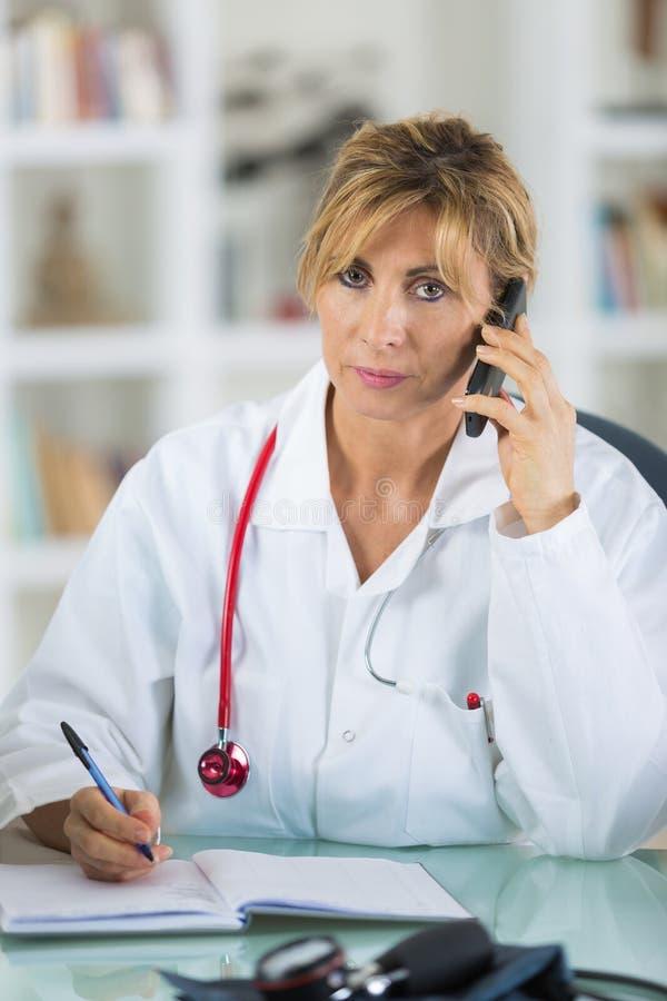 Ładna młoda uśmiechnięta kobiety lekarka na telefonie zdjęcie stock