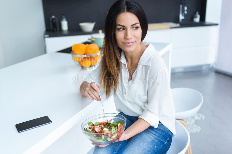Ładna młodej kobiety łasowania sałatka podczas gdy siedzący na krześle w kuchni w domu fotografia stock