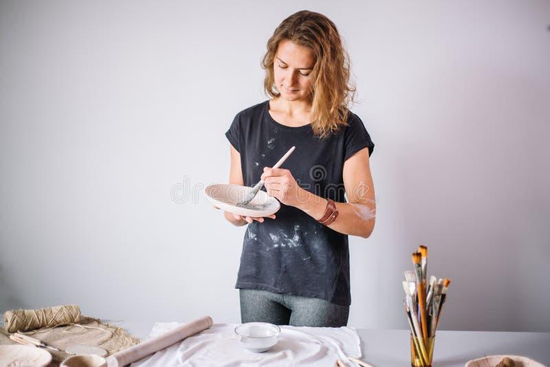 Ładna młodej kobiety garncarka maluje glinianą filiżankę Kobieta pracuje W jej ceramicznym studiu obraz stock