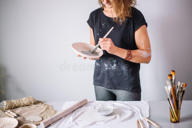 Ładna młodej kobiety garncarka maluje glinianą filiżankę Kobieta pracuje W jej ceramicznym studiu obraz royalty free
