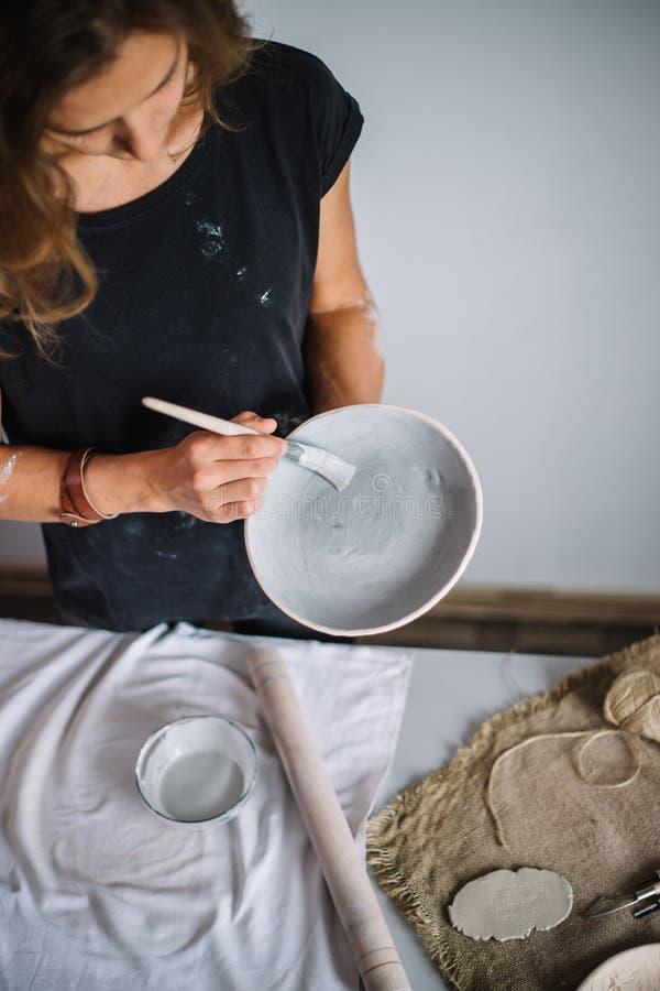 Ładna młodej kobiety garncarka maluje glinianą filiżankę Kobieta pracuje W jej ceramicznym studiu fotografia stock