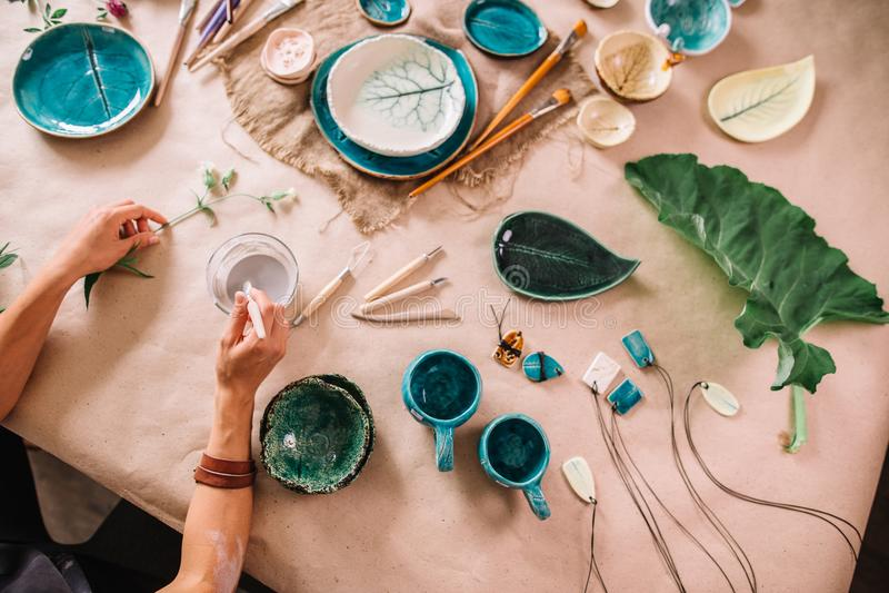 Ładna młodej kobiety garncarka maluje glinianą filiżankę Kobieta pracuje W jej ceramicznym studiu zdjęcie royalty free