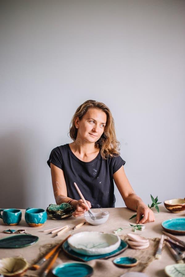 Ładna młodej kobiety garncarka maluje glinianą filiżankę Kobieta pracuje W jej ceramicznym studiu obrazy royalty free