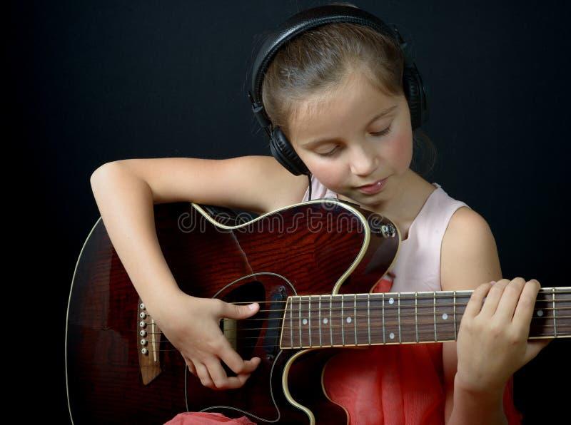 Ładna mała dziewczynka bawić się gitarę fotografia stock