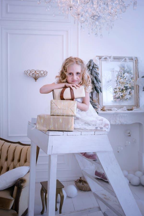 Ładna mała dziewczynka był oparta na prezentów pudełkach zdjęcie stock