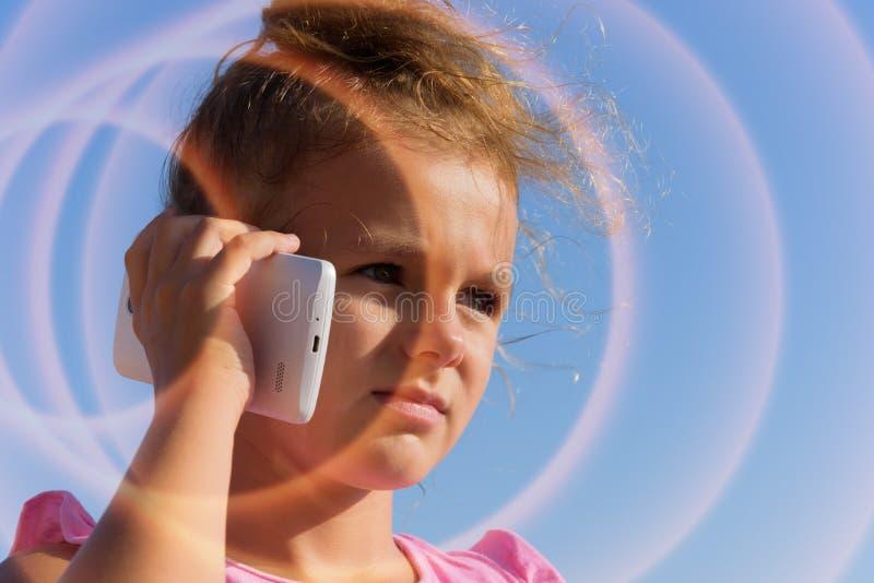 Ładna mała dziewczynka mówi smartphone, mruży w świetle słonecznym na niebieskiego nieba tle Smartphon jest bieg fala zmierzchem  zdjęcia stock