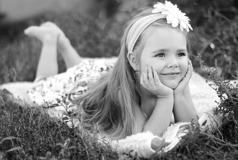 Ładna mała dziewczynka na zielonej trawie fotografia royalty free