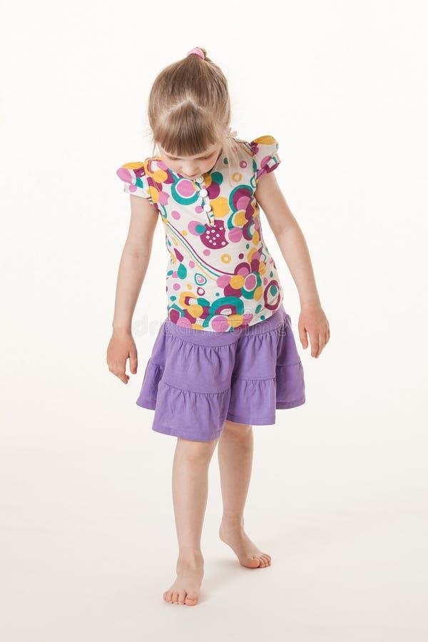 Ładna mała dziewczynka patrzeje pod jej nogami zdjęcie royalty free