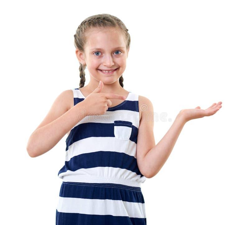 Ładna mała dziewczynka w pasiastej sukni pokazuje coś na palmie, pracowniany portret, biały tło zdjęcia royalty free