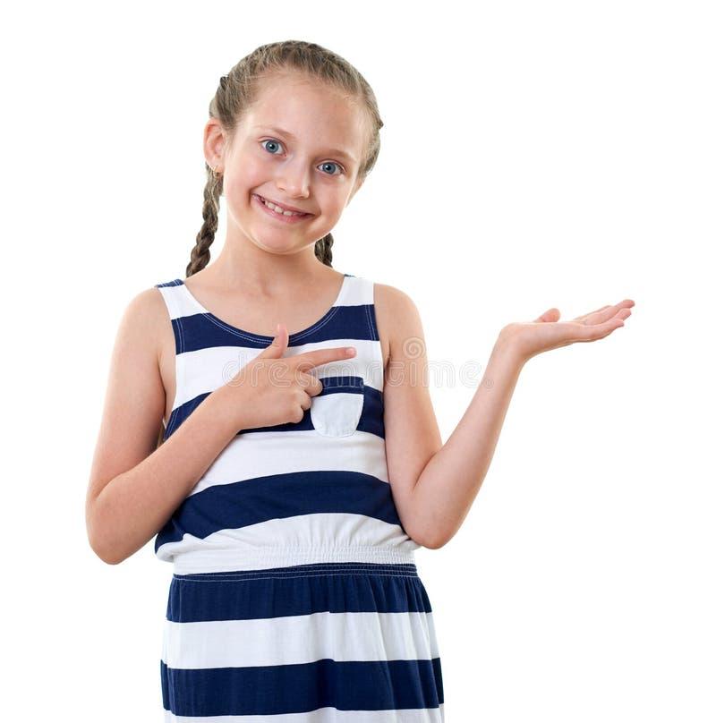 Ładna mała dziewczynka w pasiastej sukni pokazuje coś na palmie, pracowniany portret, biały tło obrazy stock