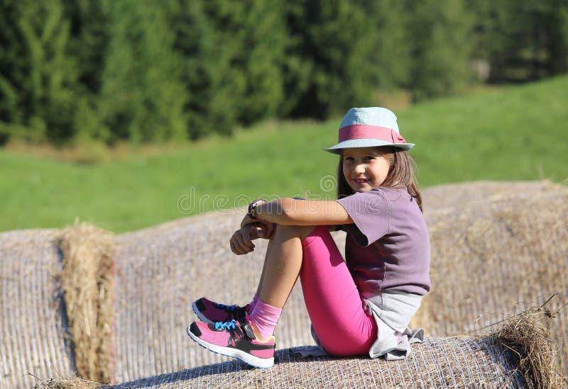 Ładna mała dziewczynka z długie włosy nadmierną siano belą w wsi fotografia royalty free