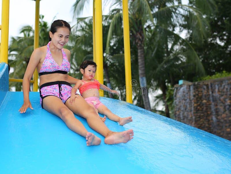 Ładna mała dziewczynka z jej matką ono ślizga się w pływackim basenie outdoors obraz royalty free