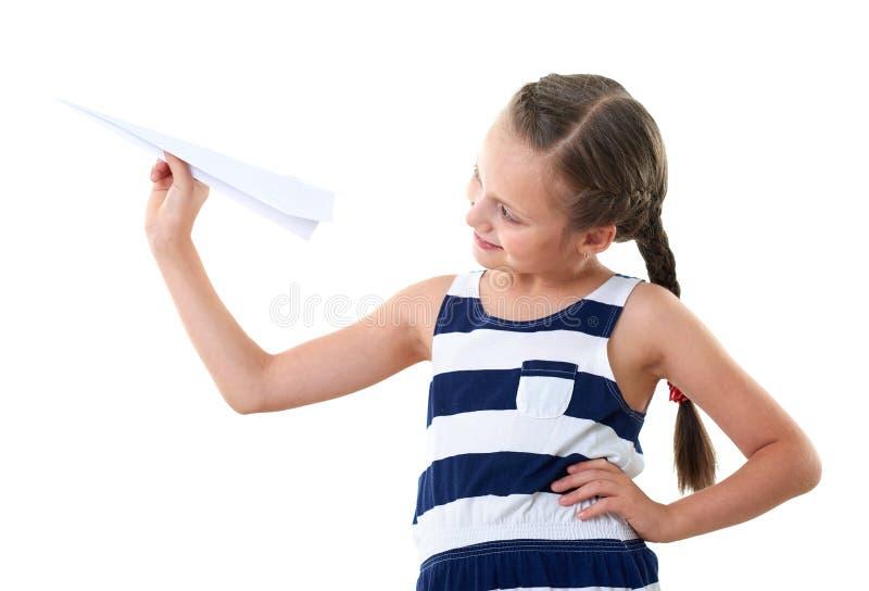 Ładna mała dziewczynka z papieru samolotem, pasiasta suknia, pracowniany portret, biały tło zdjęcie stock