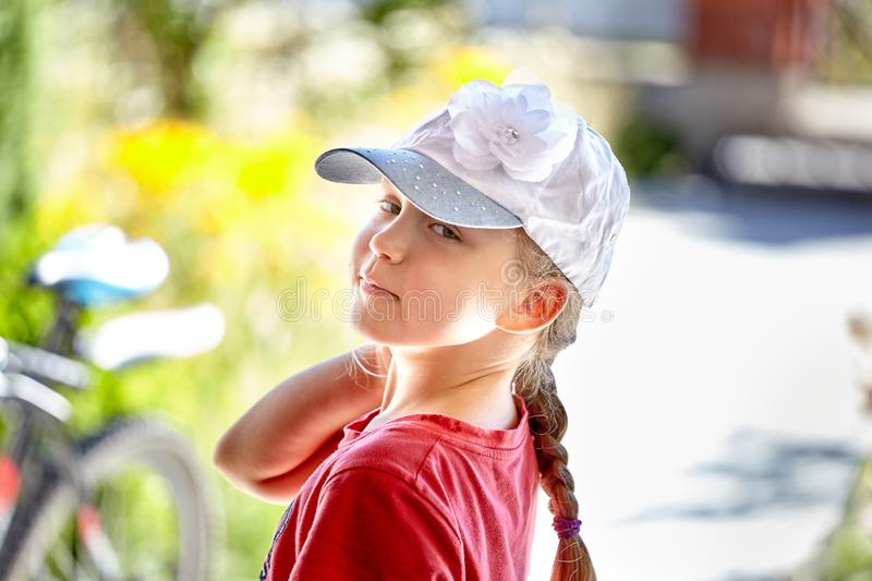 Ładna mała dziewczynka z zielonymi oczami w białej nakrętce i patrzeć obraz royalty free