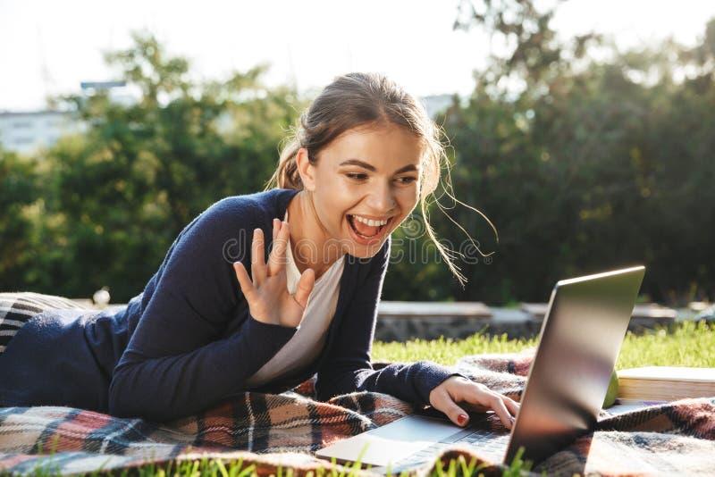 Ładna nastoletnia dziewczyna kłaść na trawie przy parkiem fotografia stock