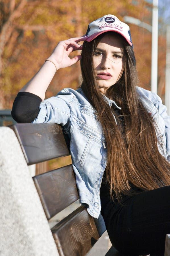 Ładna nastoletnia dziewczyna na ławce fotografia stock