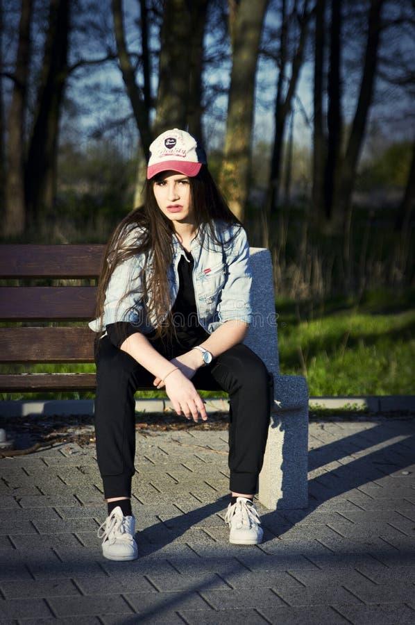 Ładna nastoletnia dziewczyna na ławce zdjęcie royalty free