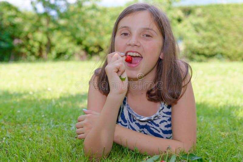 Ładna nastoletnia dziewczyna outdoors z wiśnią zdjęcia royalty free
