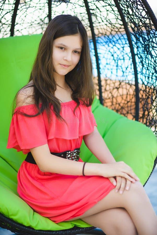 Ładna nastoletnia dziewczyna relaksuje na lounger outdoors fotografia stock