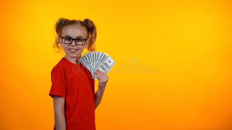 Ładna nastoletnia dziewczyna w widowiskach pokazuje wiązkę dolarowi rachunki, zarabia pieniądze zdjęcia stock
