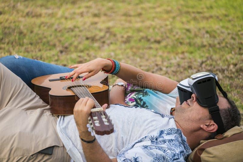 ?adna nowo?ytna pary kobiety i m??czyzny sztuki caucasian gitara i u?ywa nowo?ytn? technologii rzeczywisto?ci wirtualnej gogle s? fotografia stock