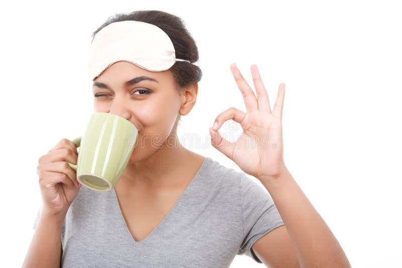 Ładna oliwkowa dziewczyna pije ok i wskazuje zdjęcia royalty free