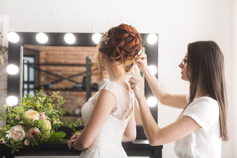 Ładna panna młoda i stylista w studiu przed ślubną ceremonią obraz royalty free
