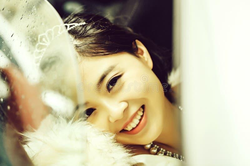 Ładna panna młoda ono uśmiecha się przez okno obraz stock