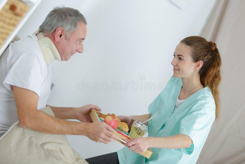 Ładna pielęgniarka daje śniadaniu uśmiechnięty starszy mężczyzna w domu fotografia stock