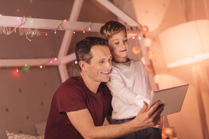 Ładna przyjemna chłopiec pozycja wraz z jego ojcem zdjęcie stock