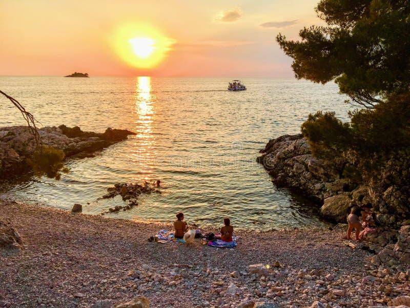 Ładna rodzina miejscowi cieszy się pięknego zmierzch wzdłuż brzeg Adriatycki morze w Rovinj, Chorwacja przy plażą w parku fo fotografia royalty free