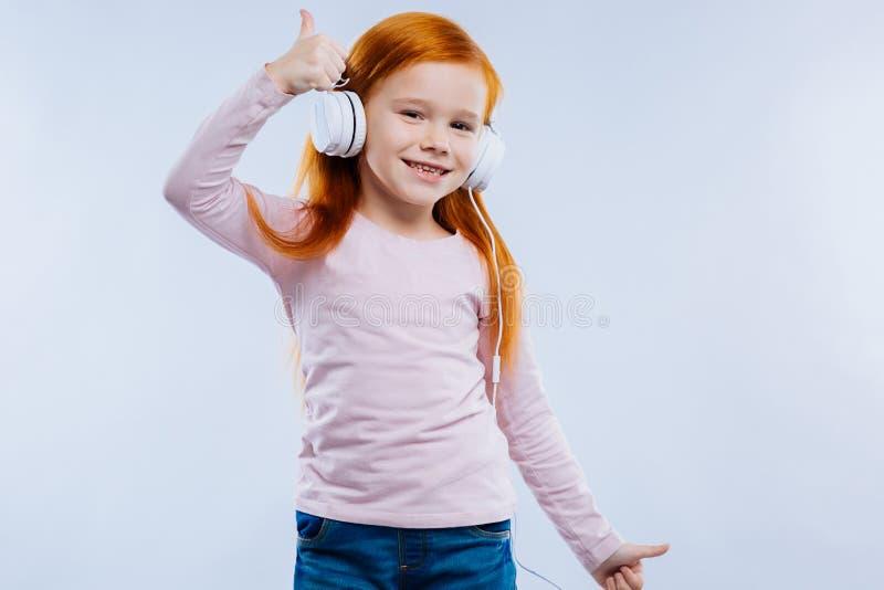 Ładna rozochocona dziewczyna pokazuje ci OK znaka zdjęcie royalty free